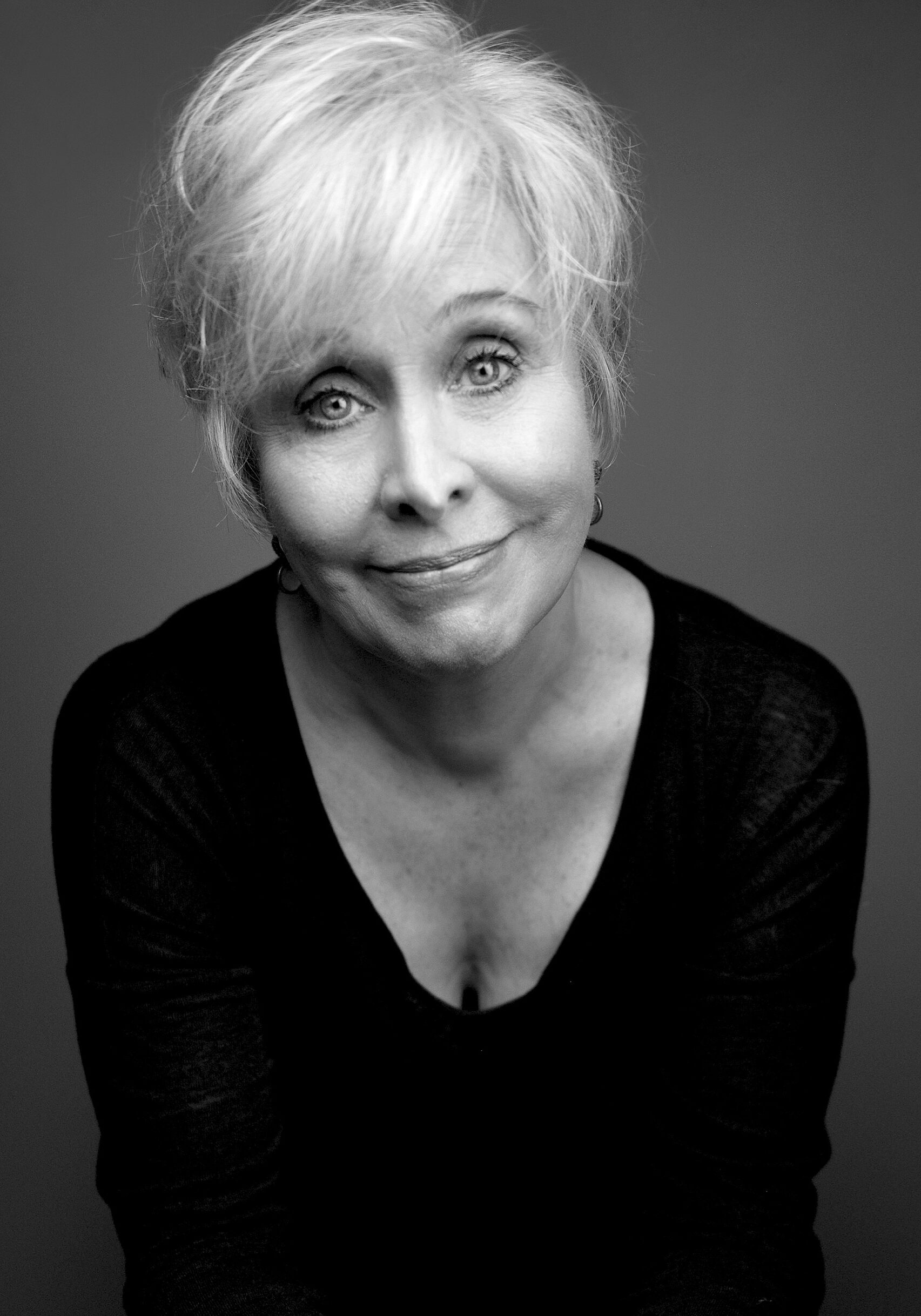 A black and white image of actress Nancy Opel wearing a black top and smiling softly at the camera.